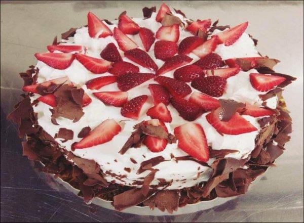 Bolo de chocolate coberto com rapas de chocolate, chantilly e morangos