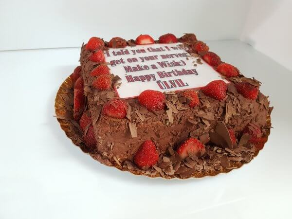 Bolo quadrado chocolate coberto com morangos e dedicatória - vista em perspetiva