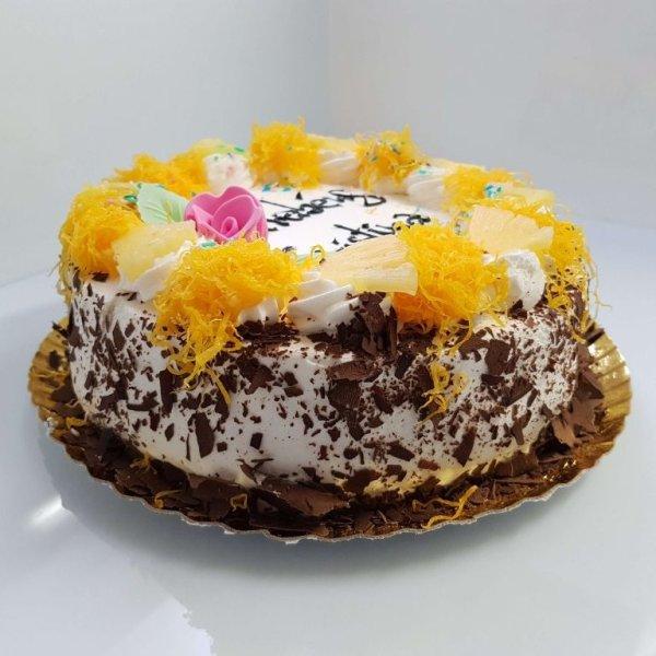 Bolo de chocolate redondo com chantilly e ananás - vista em perspetiva