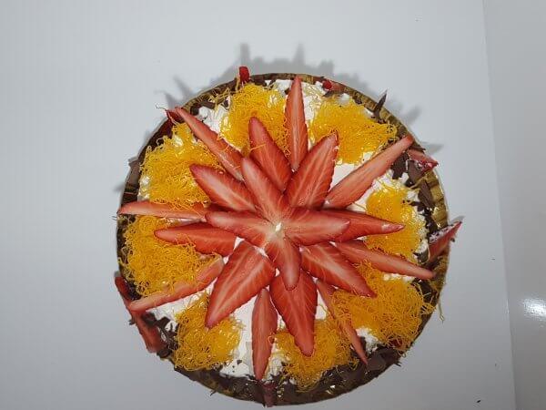 Bolo coberto com chantilly, morangos e fios de ovos - vista de cima