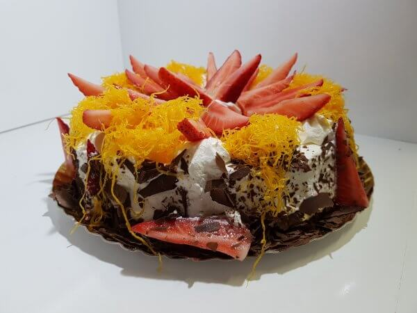 Bolo coberto com chantilly, morangos e fios de ovos - vista em perspetiva